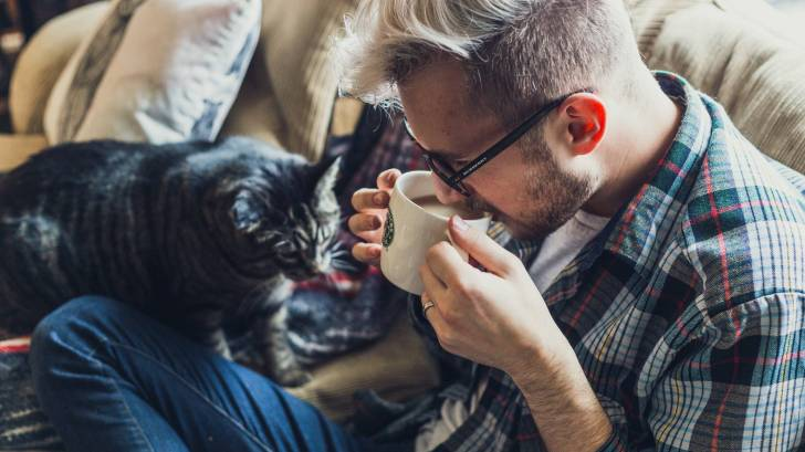 man drinking coffee with his cat