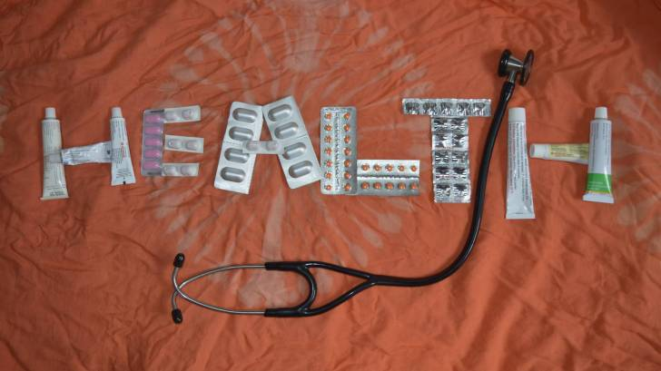 health sign made with pills and lotions and a stethoscope