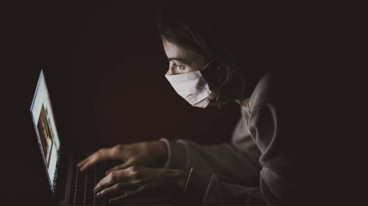 person with a mask on looking at a computer screen