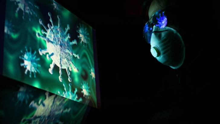 researcher looking at the coronavirus with a mask on