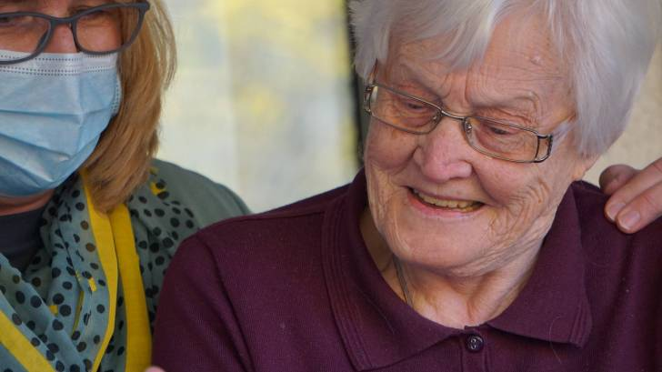 health care worker look at test results with a resident of the nursing home