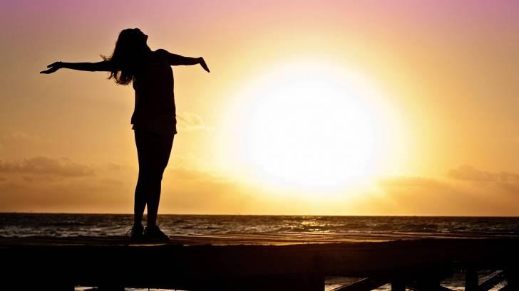 woman celebrating the sun rising, vitamin d natural