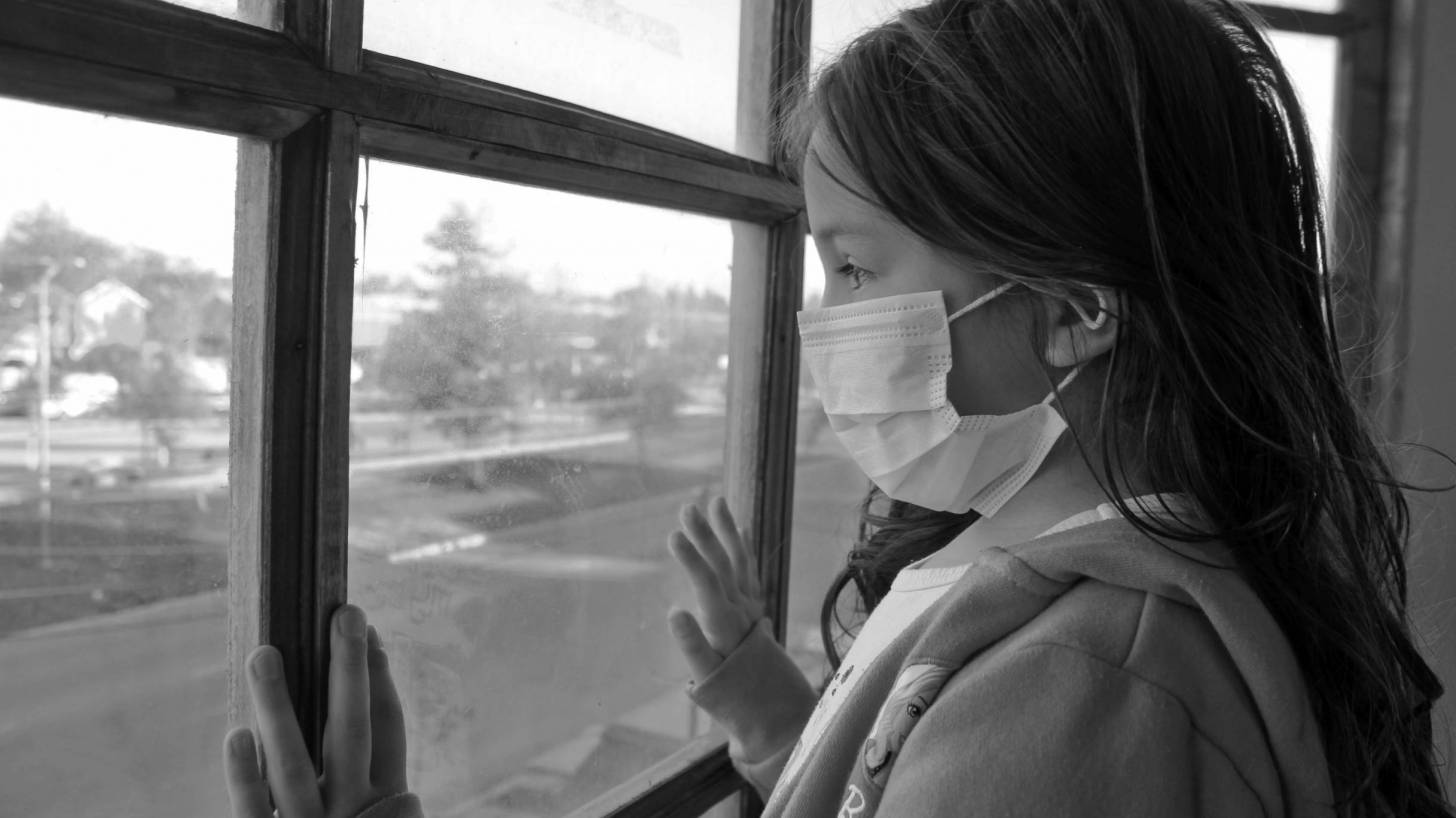 young girl looking out a window with a mask on