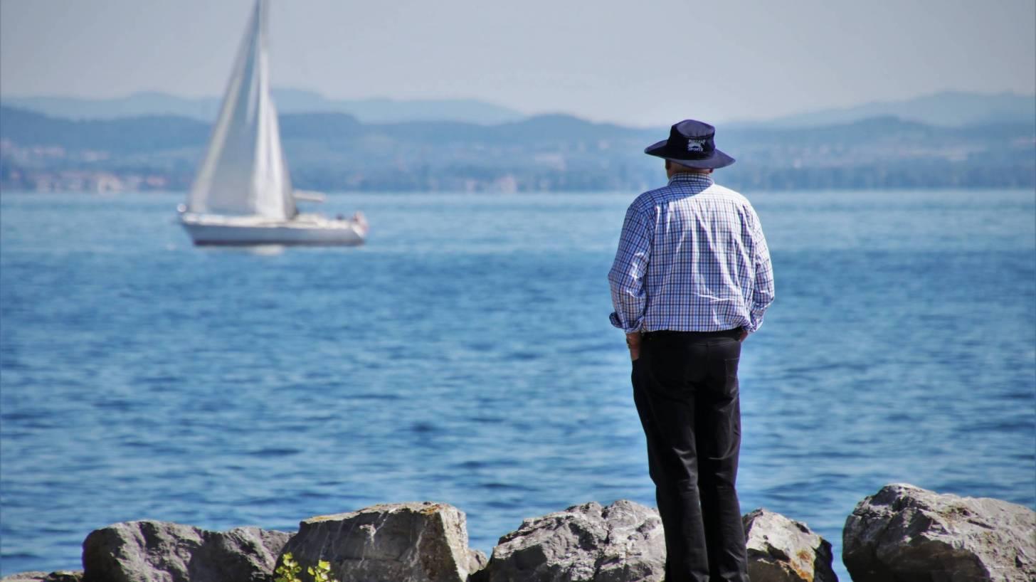 senior man looking out at a sailboat on a lake