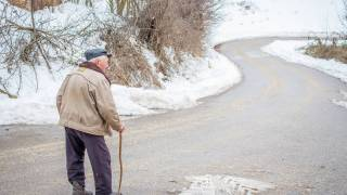 Older man walking on a snowy road