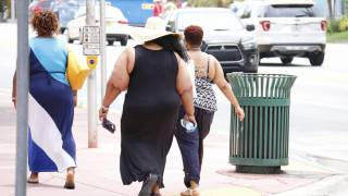 backs of obese people walking away