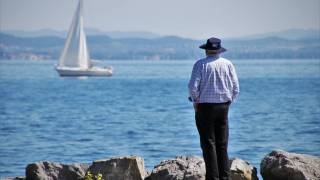 senior man looking out at a sailboat on a lake