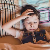 young boy in bed with a thermometer taking his temp