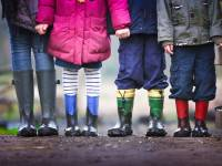 children standing together, with rain boots on