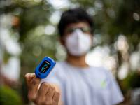 young man with a mask on taking his oxygen level